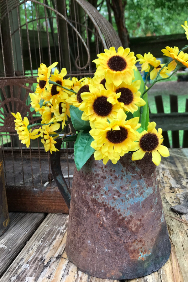 Rusty garden containers are perfect for fall flowers. Yellow sunflowers, or orange zinnias, look so pretty against the brown rust.