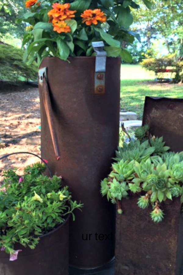 Add a little whimsy to your garden with rusty garden containers full of flowers and succulents